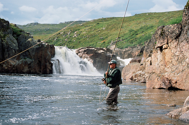 A Salmon angler fly fishing in the Falls Pool on the Eastern Litza River. Kola Peninsula, NW Russia.