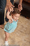 13 month old baby girl at home walking holding onto father's fingers vertical