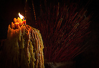 Large Candle and Incense burning at the temple ruins of EK Phnom, Battambang area, Cambodia