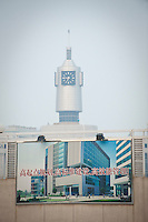 Daytime vertical view of a construction site and the Tianjin Railway Station clock in the background in the Hebei District in Tiānjīn.  © LAN