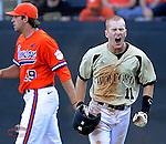 Shortstop Derek Hirsch (11) of the Wofford College Terriers shouts after sliding home to score the final run of a 7-run first inning in a game against the Clemson Tigers on Tuesday, May 5, 2015, at Russell C. King Field in Spartanburg, South Carolina. In the background is Clemson pitcher Brody Koerner. Wofford won, 17-9. (Tom Priddy/Four Seam Images)