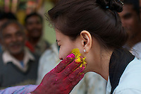 Tourist getting her share of color during Pre Holi Festival in Old Delhi India