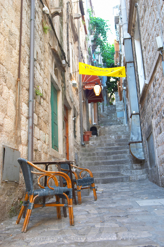 View from the Prijeko street up a narrow street with steep stairs. Two rattan chairs and a table on the cobble stone street. Dubrovnik, old city. Dalmatian Coast, Croatia, Europe.