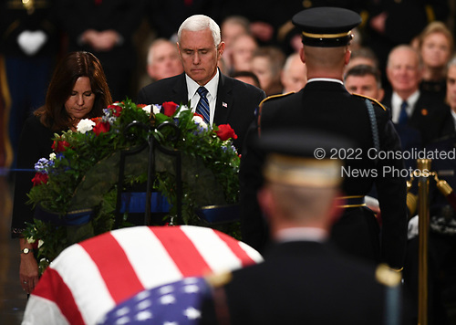 US Vice President Mike Pence (C) and Second Lady of the United States Karen Pence (L) pay their respects at the casket bearing the remains of former US President George H.W. Bush at the US Capitol during the State Funeral in Washington, DC, December 3, 2018. - The body of the late former President George H.W. Bush travelled from Houston to Washington, where he will lie in state at the US Capitol through Wednesday morning. Bush, who died on November 30, will return to Houston for his funeral on Thursday. (Photo by Brendan Smialowski / AFP)
