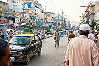 A photo of a street scene with crowds of pedestrians old buildings pollution and vehicles from the old and ancient city of Rawalpindi in Pakistan
