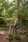USA, Oregon, Oregon Cascades, young boy stands by a trail sign in the in the Wilamette National Forest in the early Fall on the hike to Proxy Falls, McKenzie Pass