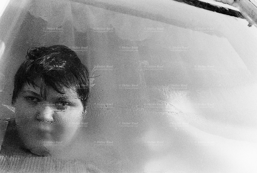 Belarus. Province of Gomel. Bolchevik. A mentaly handicapped boy, 15 years old, behing his window at home. He suffers physical problems due to the Chernobyl disaster. The village of Bolchevik was heavily affected by the fallout of the catastrophe which took place on april 1986 at 1.23 am in the Chernobyl atomic power station. The accident in the nuclear power plant has environmentals effects which affect territories and health of the people. The village of Bolchevik is still contamined by radioactive materials, like caesium 137.  © 2006 Didier Ruef