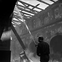 Eglise de Lalande, chemin de l'Eglise-de-Lalande. 20 juin 1961. Vue intérieure de l'église pendant l'incendie : au 1er plan pompier avec casque de dos, tient une lance à eau ; en arrière-plan intérieur de l'église et toit détruit. Cliché pris pendant l'incendie qui a ravagé l'église de Lalande.