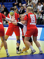 31 MAR 2010 - LONDON, GBR - Britains Nina Heglund (in white) tries to shoot despite her path being blocked by the Icelandic defence in the two teams 2010 European Womens Handball Championships qualifier (PHOTO (C) NIGEL FARROW)