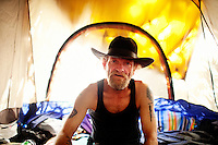 """Ventura, California, July 23, 2010 - A portrait of Tim 'Timbow' Bowman in his tent that is hidden by the 16-foot tall grass and bamboo on the Ventura River bottom. Bowman has been homeless and living along the river since the early 1990's. """"All I need is a little peanut butter and a little bud and I am fine,"""" says Bowman. He has a medical permit to smoke from an injury sustained while working construction.  . In 1987 Bowman's 18-month-old daughter, Miranda Laurel, died from Lyme disease. His wife left him soon afterwards. A year later he fell through a plate glass window while working on a construction site, leaving him disabled and unable to work construction. He says the loss of his wife and daughter and his struggles with work sent him into a spiral. He eventually lost his home. He says he lives in the 300+ community along the river bottom because he """"feels at home."""" Adding, """"I feel loved down here. Up there is nothing but trouble."""" The two-mile stretch of river bottom from the Pacific to Stanley Road is home to about 300 homeless, who have carved tunnels and paths into the tall grass and bamboo. Bowman, who survives off of SSI, says, """"I lead an honest life. I don't steal, I don't rob and I share whatever I can."""" .."""