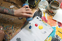 Artist and illustrator Jada Fitch mixes paint at a worktable in her living room, which doubles as her art studio, in Portland, Maine, USA, on Fri., July 28, 2017. Fitch has recently been making birdhouses that look like living rooms with small portraits of birds. The birdhouses sell out within minutes on her Etsy store.