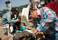 A pair of cowboys prepare to buck a horse during the Miles City Bucking Horse Sale at the Eastern Montana Fairgrounds in Miles City Montana Sat., May 19, 2007. Saddle broncs and bareback broncs are auctioned off after they are bucked.