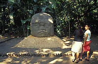 Two young women in front of a Colossal Olmec head, Monument 1 at the Parque Museo Laventa in Villahermosa, Tabasco. Mexico. This outdoor archaeology museum and ecological park was created by Mexican poet Carlos Pellicer in 1957.