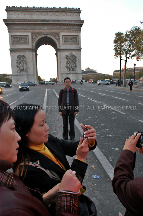11/8/2005--Paris, France..Chinese tourists stop to take photos along the Champs Elysees in front of the Arc de Triomphe in Paris. After 12 nights of rioting in France officials are worried that tourists will stop visiting France although most of the rioting is far away from the popular tourist destinations. In Paris there was heavy police presence around many of the popular tourist sites..Photograph By Stuart Isett.All photographs ©2005 Stuart Isett.All rights reserved.