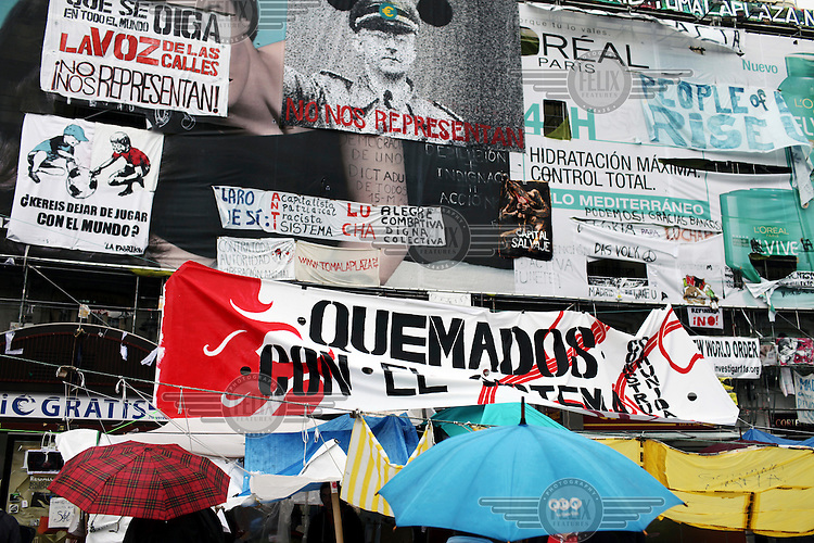 Banners and signs cover the walls of Puerta del Sol. In May 2012, following a worsening financial crisis and a deepening recession in Spain, thousands of people started to gather in Spanish cities to protest against austerity, the global financial system, high unemplyment rate (Spain's is the highest rate in Europe) and the lack of opportunities. The protest movement has become known as 'los indignados' (the indignant ones).