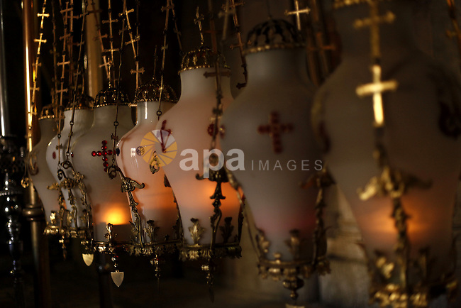 Crosses and candles are seen at the Church of the Holy Sepulchre in Jerusalem's Old City, June 26, 2013. The Church of the Holy Sepulchre is one of the most Holy sites in the Christian world and its site in Jerusalem is identified as the place both of the crucifixion and the tomb of Jesus of Nazareth. The church has long been a major pilgrimage center for Christians all around the world. Photo by Saeed Qaq