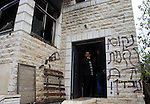 A member of the Hamayel family flashes a victory sign at the entrance of his damaged home, that was attacked and burnt by suspected Jewish extremists using petrol bombs, in the village of Abu Falah, northeast of Ramallah, on November 23, 2014. Suspected Jewish extremists firebombed a house in a Palestinian village in the occupied West Bank early, its mayor said, pointing the finger of blame at local settlers. Masud Abu Mura, mayor of Khirbet Abu Falah, said four women were inside the house at the time, but they all escaped unharmed. Photo by Shadi Hatem
