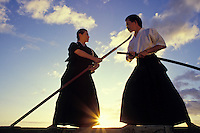 Man and woman give a kendo demonstration, a Japanese martial art, at sunset