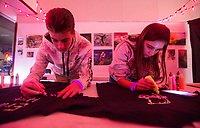 NWA Democrat-Gazette/BEN GOFF @NWABENGOFF<br /> Mason Sage of Bentonville and Erika Mansfield of Rogers decoate T-shirts with glow-in-the-dark paint Thursday, Nov. 8, 2018, at Rogers Experimental House during the 'Light Up the Night!' one year anniversary Art on the Bricks art walk in downtown Rogers. More than 25 artists and musicians opened pop-up galleries selling their artwork at downtown shops and restaurants. Go Downtown Rogers hosts the walks on the second Thursday of each month.
