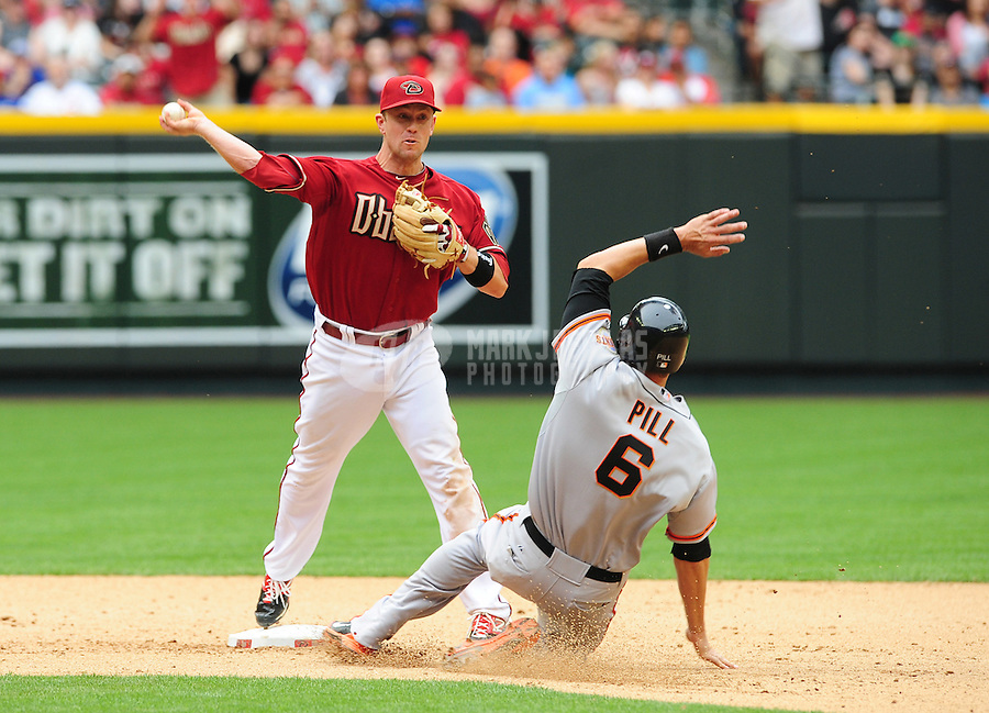 Apr. 8, 2012; Phoenix, AZ, USA; Arizona Diamondbacks second baseman Aaron Hill throws to first to complete the double play after forcing out San Francisco Giants base runner Brett Pill in the eighth inning at Chase Field. Mandatory Credit: Mark J. Rebilas-