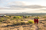 TANZANIA, Two Maasai men wearing red traditional cloths, walking in Shumata camp, Arusha National Park