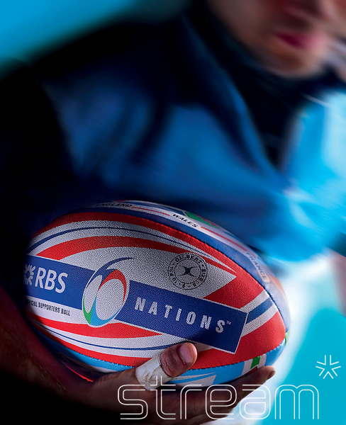 Blurred rugby player carries 6 Nations rugby ball.
