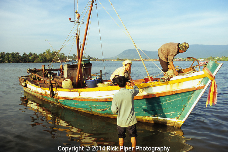 Man buying fish from Cham fishing boat, at dawn on the Sanke river, Kampot, Cambodia.