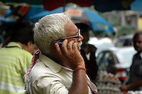 An old Indian man using a mobile phone on a road of  Kolkata, West Bengal,  India  7/18/2007.  Arindam Mukherjee/Landov