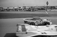 The Lowenbrau Porsche 962 of Al Holbert, Derek Bell , and Al Unser Jr and the #34 Porsche 934 of Kikos Fonseca, Luis Mendez, and Enrique Molins race past the pits during the 24 Hours of Daytona, Daytona International Speedway, Daytona Beach, FL, February 2, 1986.  (Photo by Brian Cleary/www.bcpix.com)