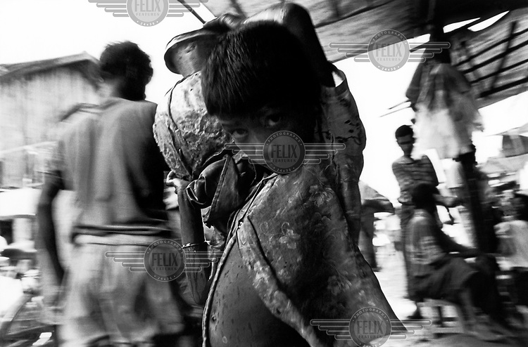 A boy carries a jug of water through the Akyab fish market.
