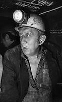 Sangerhausen / DDR - 1989.Miniera di rame Thomas Munzer. 700 metri di profondità. Con i minatori a bordo di un trenino che porta gli operai nella zona di estrazione, sul fronte della miniera. Si viaggiava per quasi un'ora in un cunicolo buio alla sola luce delle lampade ad acetilene. Poi si proseguiva carponi. Le gallerie erano alte un metro. Le ginocchia affondavano nel fango. Le squadre di minatori lavoravano 24 ore suddivisi in turni di 8 ore. A causa delle dure condizioni di lavoro, numerosi operai si ammalavano di silicosi e reumatismi ed andavano in pensione in anticipo. In compenso i loro stipendi erano i più alti della DDR. Dopo la reunificazione della Germania la miniera Thomas Munzer è stata chiusa..Foto Livio Senigalliesi..Sangerhausen / DDR - Dec.1989.Thomas Munzer copper mine. In a tunnel 700 meters depth. Workers on board a small train that brought them to work on the front of the mine. Working conditions were very hard. They worked on their knees in the dark using the lamp of acetylene. Teams of miners worked 8 hours in 3 shifts. After the unification of Germany Thomas Munzer copper mine was closed and has now become a museum..Photo Livio Senigalliesi.