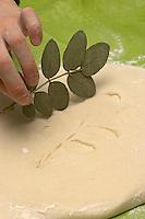 Kinder basteln Blattkacheln aus Salzteig, Junge macht einen Abdruck von einem Rosenblatt auf den Salzteig