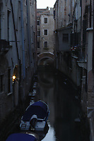 Early morning low light image of narrow canal at dawn,showing solitary boat, Venice, Italy.