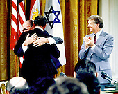 United States President Jimmy Carter, right, applauds as President Anwar Sadat of Egypt, center, and Prime Minister Menahem Begin of Israel, left, hug during the signing ceremony for the Camp David Accords in the East Room of the White House on September 17, 1978..Credit: Arnie Sachs / CNP