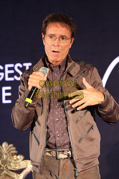 SIR CLIFF RICHARD .holds Press Conference to announce new album of soul duets at Gilgamesh, Camden, London, March 7th 2011..half length glasses grey gray shirt smiling brown speaking microphone jacket hand .CAP/ROS.©Steve Ross/Capital Pictures