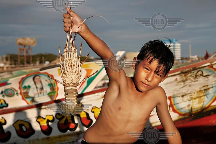 A boy holds a lobster at a beach near Playas.