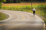 Amishman riding bicycle on country road.