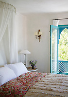 The bed is dressed with crisp white pillows, a comfortable paisley print duvet and a Moroccan wool rug
