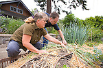 """Andrew and Patricia Nimelman cosult with Donna Smith (otherwise known as """"Your Backyard Farmer) at their home in NE Portland, OR.  Donna showing Andrew how to properly harvest and dry shallots."""