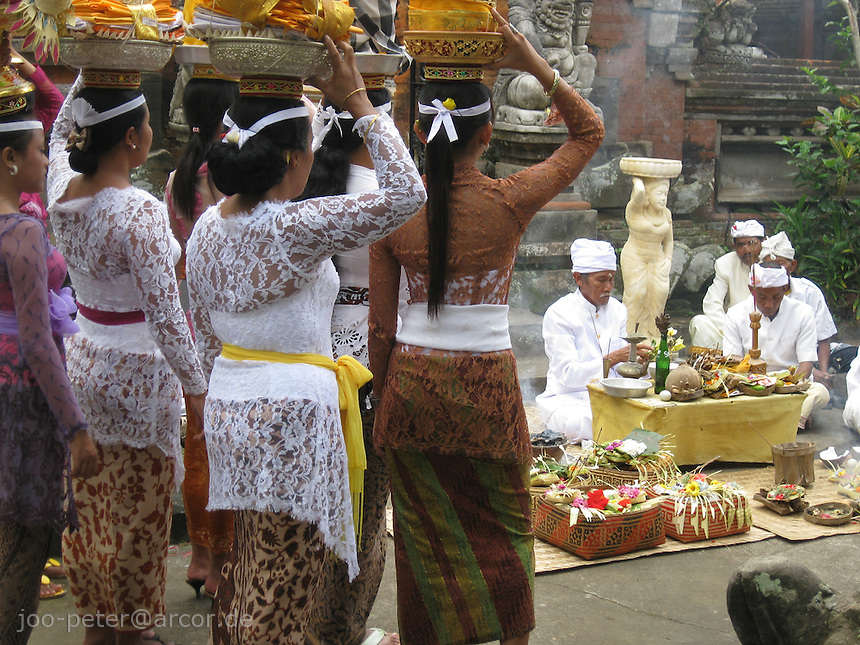 woman carryting offerings in courtyard of a temple while a priest (pendeta) performes rituals and prayers, North of Ubud, Bali, archipelago Indonesia