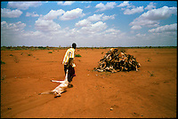 Kotulo, NE Kenya, March 2006.Nur Ali Hilow drags a dead goat from his decimated herd onto a heap of carcasses 2 meters high on the edge of town. In certain parts of East Africa, it hasn't rained for more than 4 years...More than 4 millions people are affected in the region by the worst drought in man's memory. The livestock is decimated and a whole lifestyle threatened.