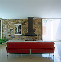 A red leather and chrome sofa faces a classic 1960's floating fireplace
