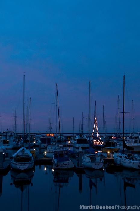 Christmas lights on fishing boat docked in Pillar Point Harbor in Half Moon Bay, California.