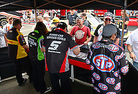 Jun. 1, 2012; Englishtown, NJ, USA: NHRA funny car drivers (R-L) Tony Pedregon, Cruz Pedregon, Alexis DeJoria and Jeff Arend sign autographs during qualifying for the Supernationals at Raceway Park. Mandatory Credit: Mark J. Rebilas-