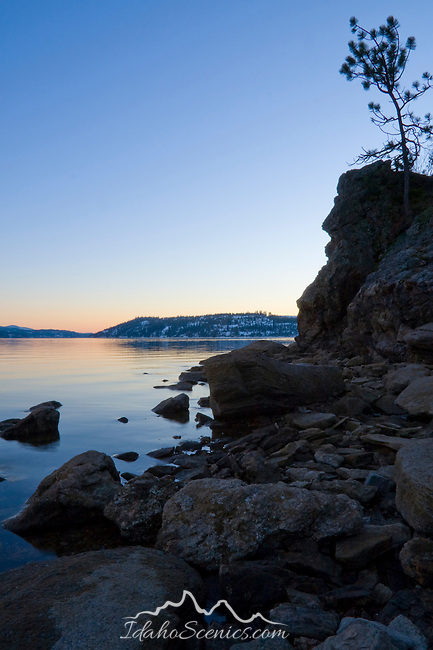 Idaho, Coeur d'Alene. Low winter water levels on Lake Coeur d' Alene reveal the rocky shoreline at dusk.