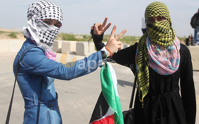 Palestinian girls flash victory sign during clashes with Israeli security forces next to the border fence with Israel, at the Erez crossing in the northern Gaza strip, on October 13, 2015. A wave of stabbings that hit Israel, Jerusalem and the West Bank this month along with violent protests in annexed east Jerusalem and the occupied West Bank, has led to warnings that a full-scale Palestinian uprising, or third intifada, could erupt. The unrest has also spread to the Gaza Strip, with clashes along the border in recent days leaving nine Palestinians dead from Israeli fire. Photo by Ashraf Amra