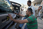 George Saadeh, 2009 Palestine speed test champion, arrives in Nablus to register his car for the following day's race. 20/05/2009. After inspection each driver is issued a number & a corresponding set of stickers for their car.