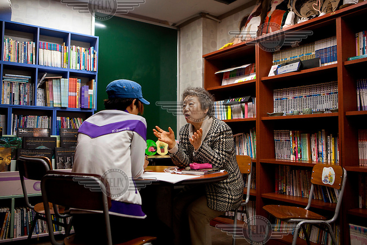Chung Soon Choi teaches Hyun Cheon Ryong, 16, (left) a North Korean defector at the Wooridal School. Many defectors from the North have had a very basic education and can find it difficult to integrate into the South Korean academic system. /Felix Features
