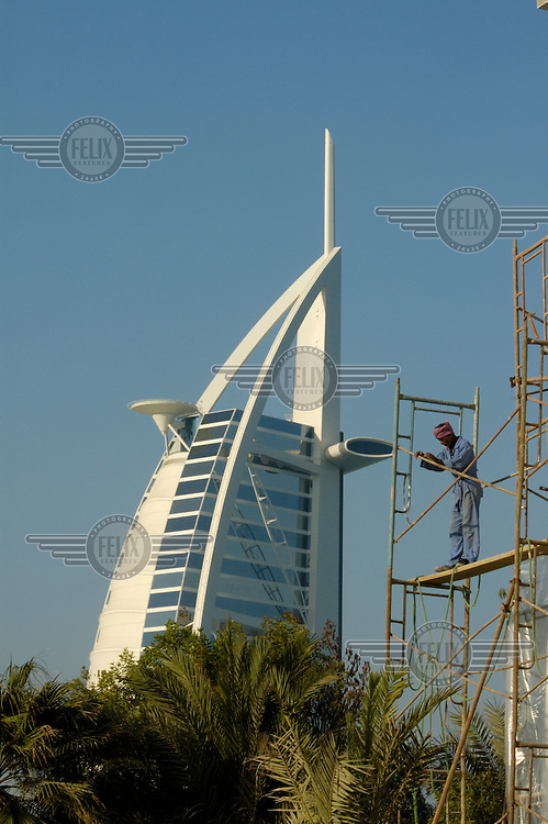 A migrant labourer works on scaffolding on a construction site in front of the Burj Al Arab 'seven star' hotel.