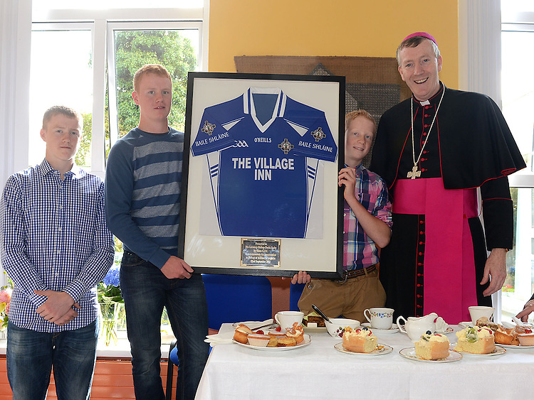 Nephews of Bishop Denis Nulty, Patrick, Brendan and Alexander Nulty present him with a Slane GFC jersey after he celebrated mass at the Church of St Patrick Slane. Photo:Colin Bell/pressphotos.ie